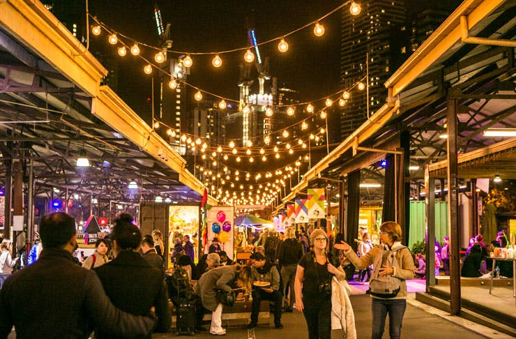 people walking through the sheds of Queen Vic Night Market.