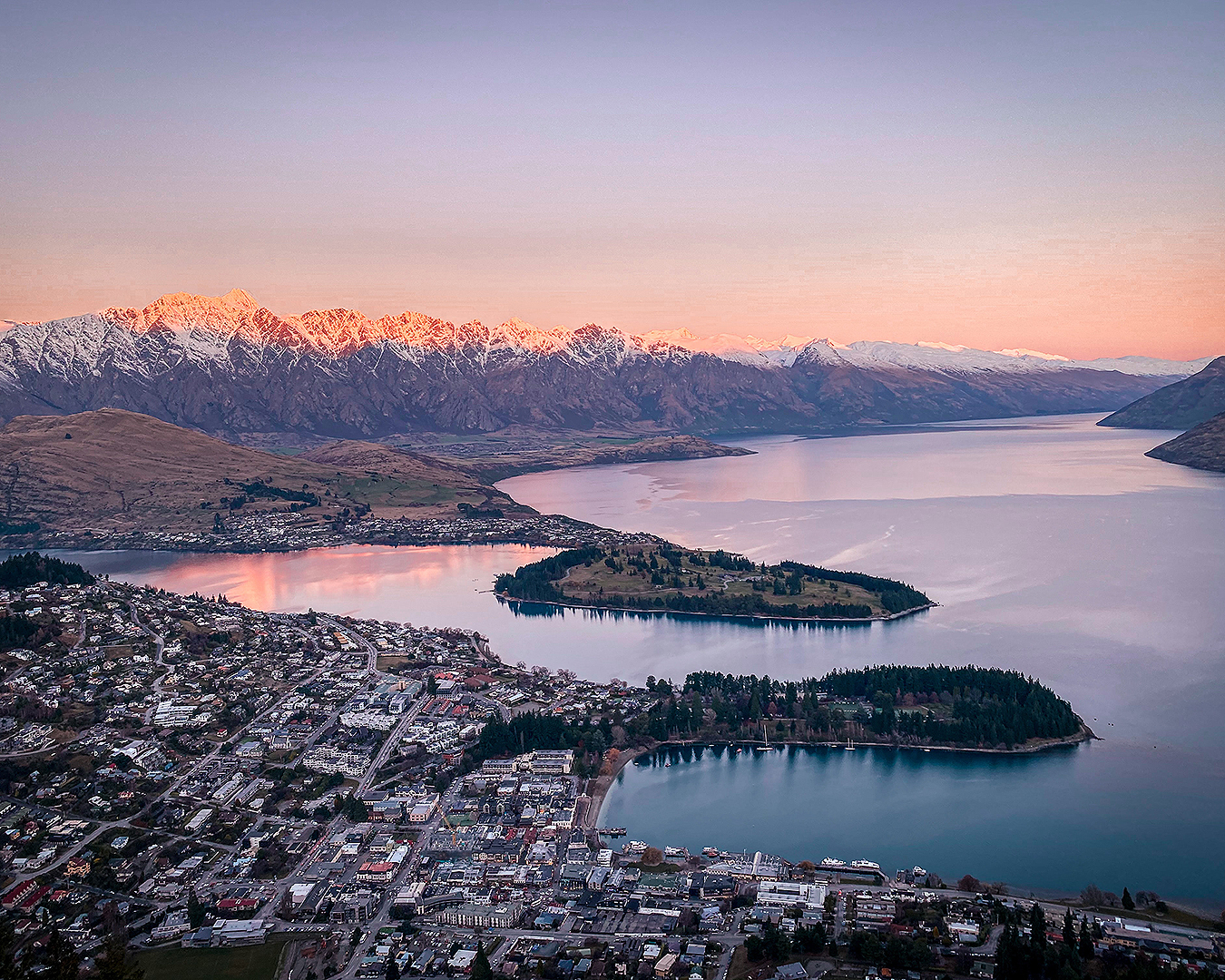 An aerial view of Central Queenstown under a gorgeous purple sky.