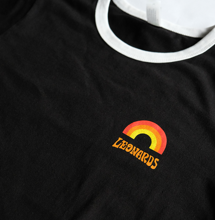 A black t-shirt with a white neckline. A logo sits on the chest which reads