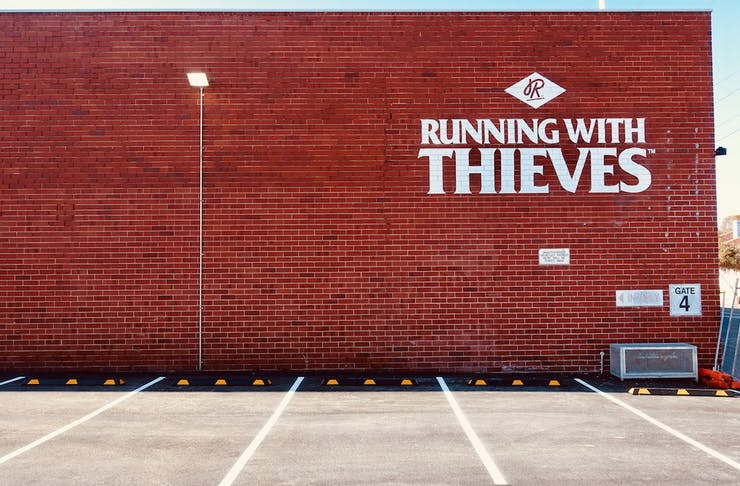 Red brick wall with Running With Thieves logo