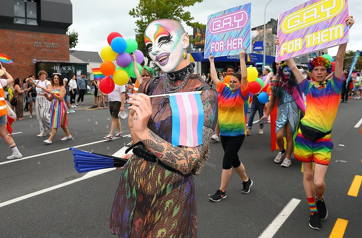 A drag queen poses fabulously while surrounded by rainbow flags on Ponsonby Road.