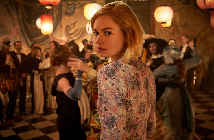Lily James as Mrs. de Winter in Rebecca looks over her shoulder in a busy room