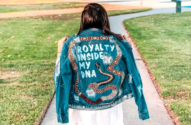 Ginny with her back to the camera wearing a jacket that reads Royalty Inside My DNA. The jacket is denim and painted with Aboriginal art.