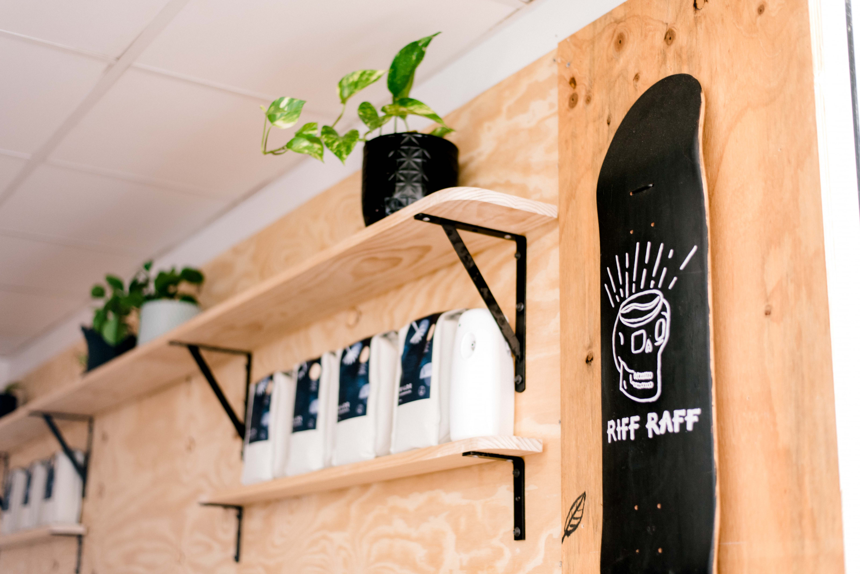 a wooden wall with wooden shelves stocked with coffee bags