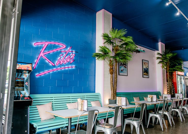 an 80s inspired diner with a pink neon sign that says