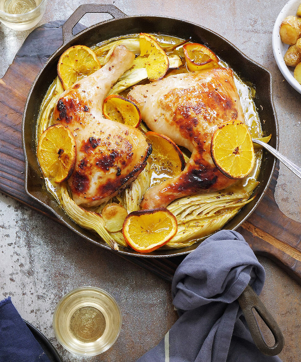 A cast-iron skillet dish with appetising chicken and lemon on a tabletop.