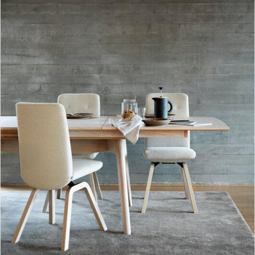 Tall white chairs surround a wooden table.