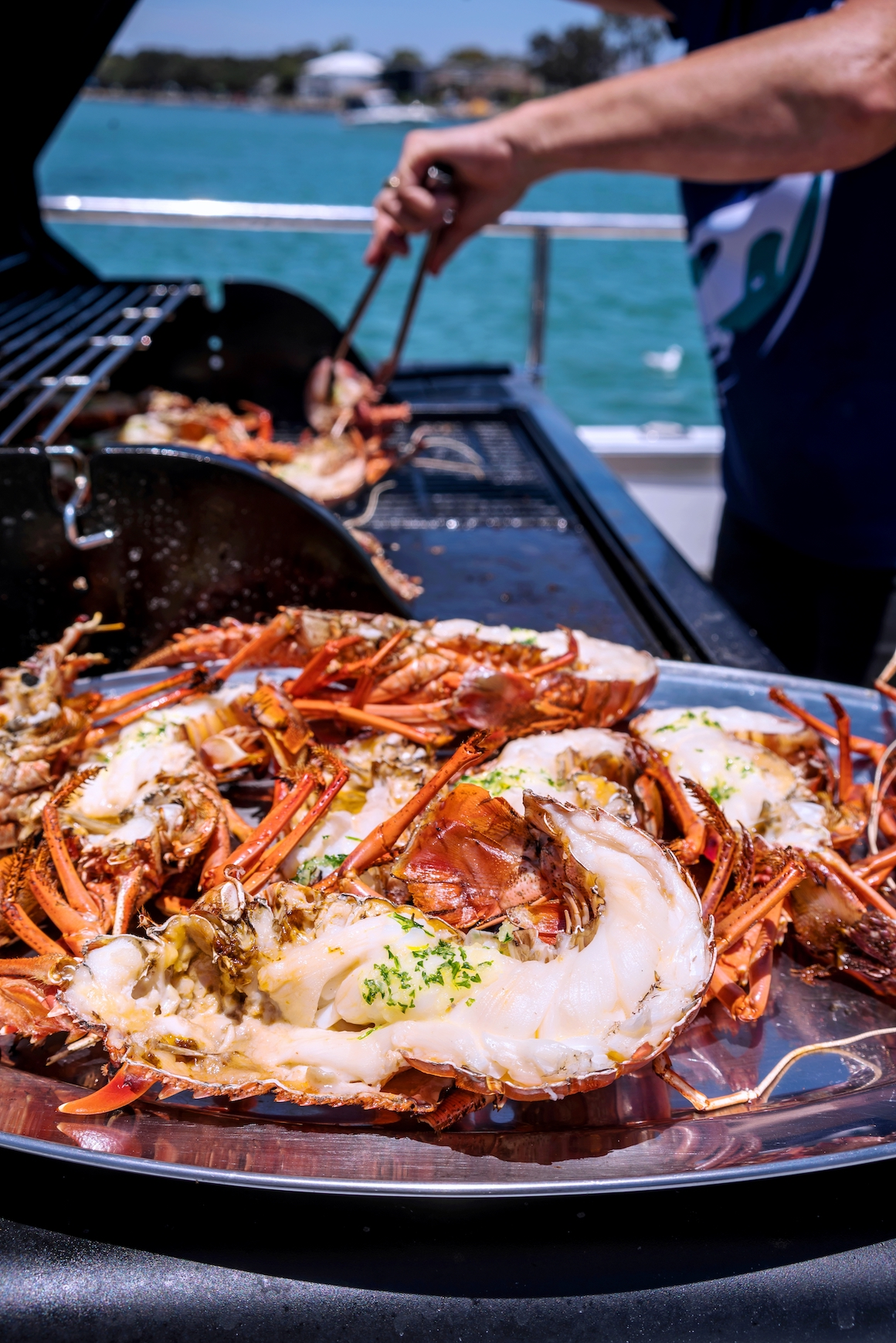 Crays being cooked on the BBQ onboard Rottnest Cruises Seafood Experience