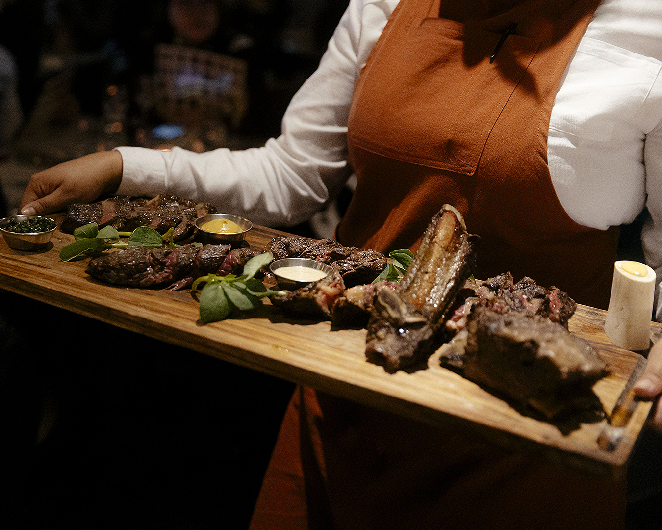 A waitress carries a massive slab of meat on a wooden board.