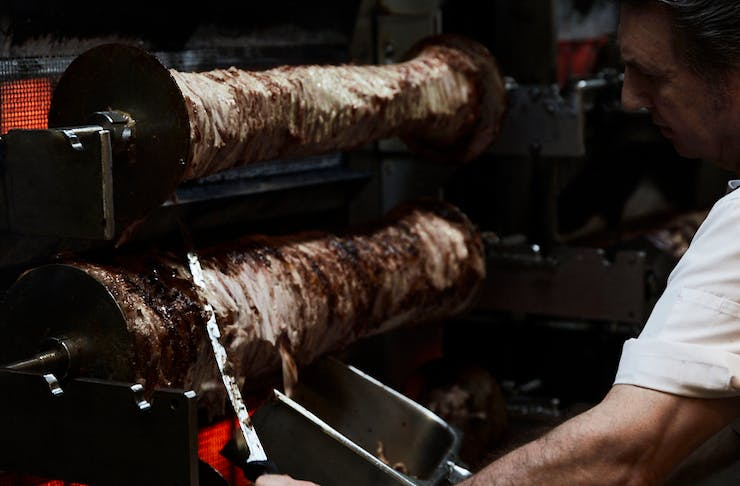 A man carving meat off in a kitchen.