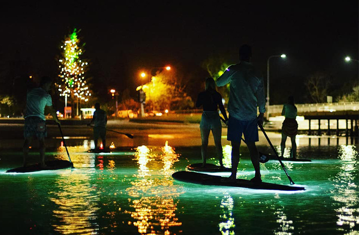 people paddle boarding on glowing paddle boards in the dark