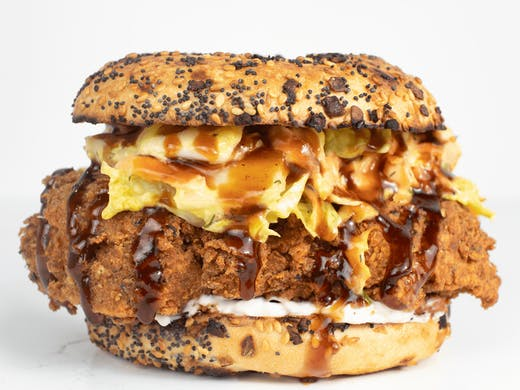 a fried chicken bagel with sauce dripping out.