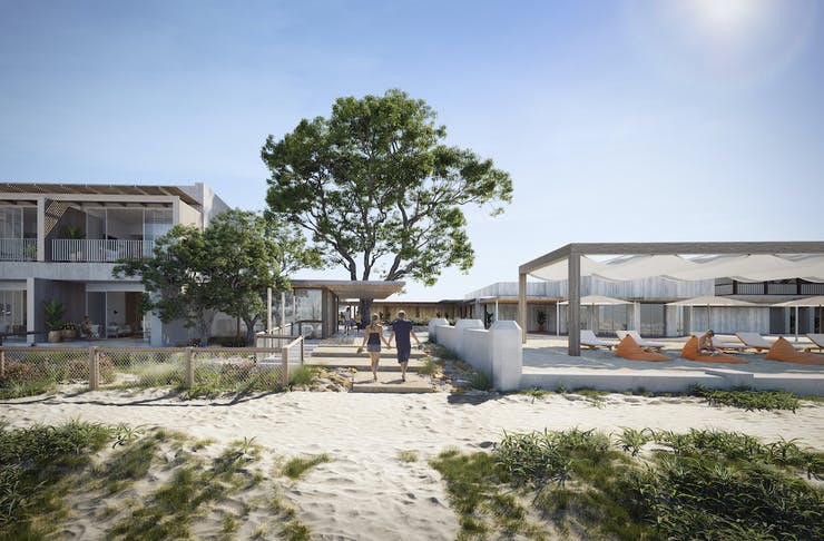 Entrance from the beach to the hotel with rooms to one side and beach loungers to the other