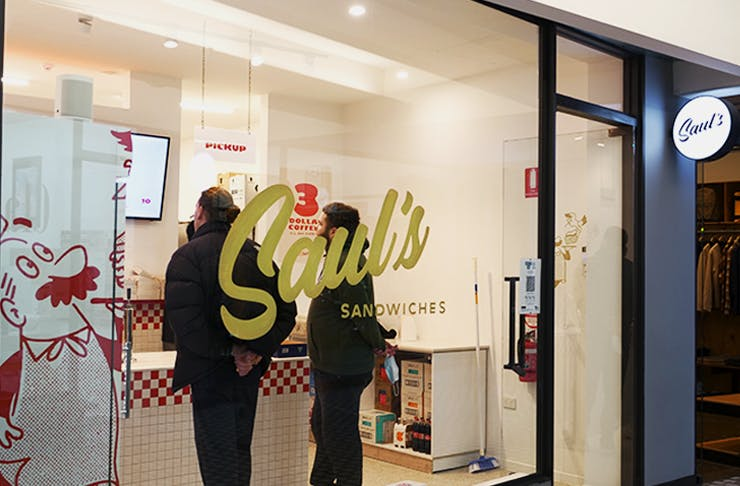 The shop front of Sauls with white paint and a gold Saul's logo on it