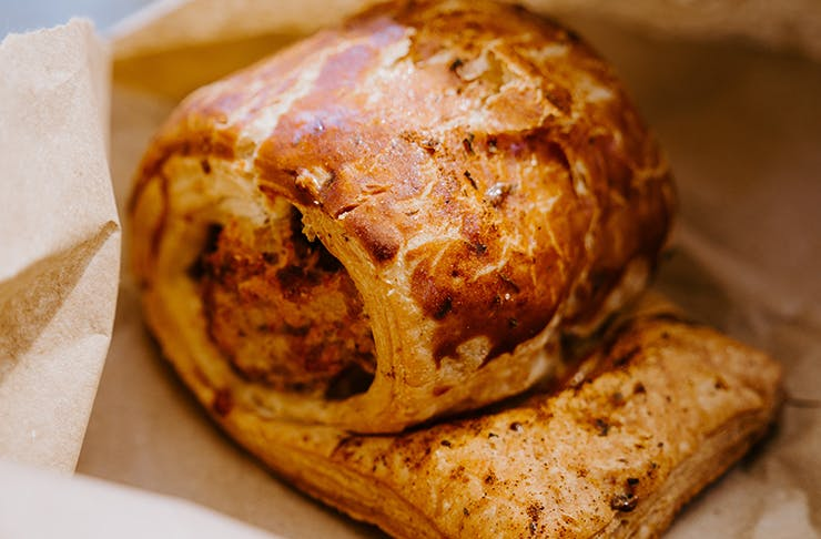 A golden sausage roll sitting on top a brown paper bag, the best sausage roll melbourne.