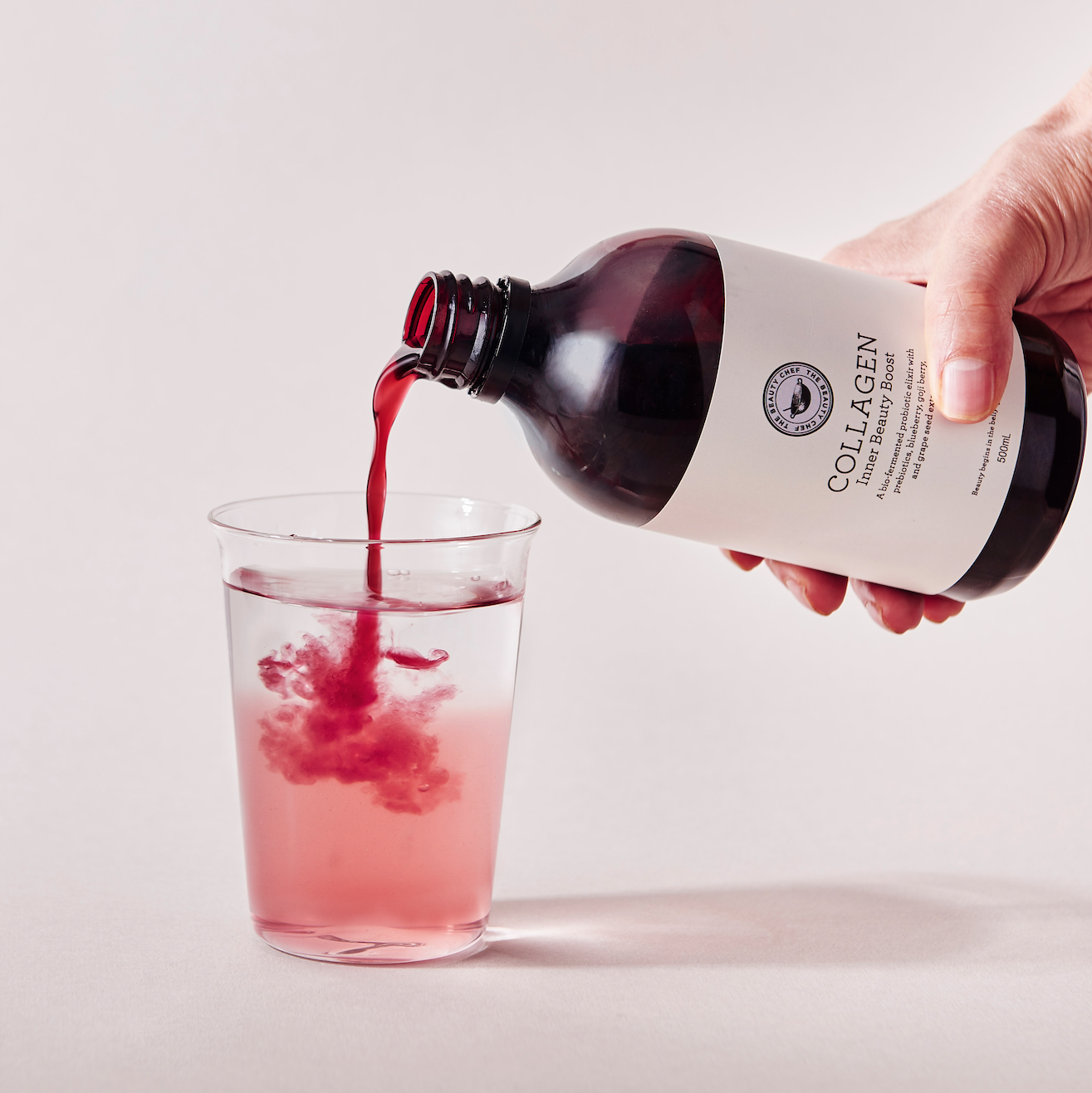 a hand pouring from a bottle into a glass