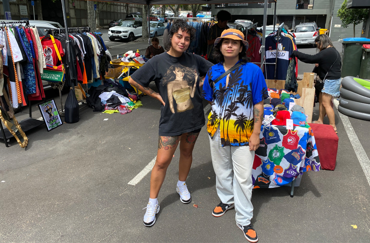 Sian and Tina stand in front of a clothing pop up store with racks upon racks of vintage clothing