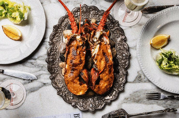 A marble table with a plate of lobster on top.