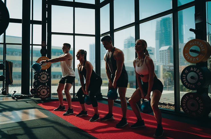 Fitness people lined up with kettlebells in front of a window.