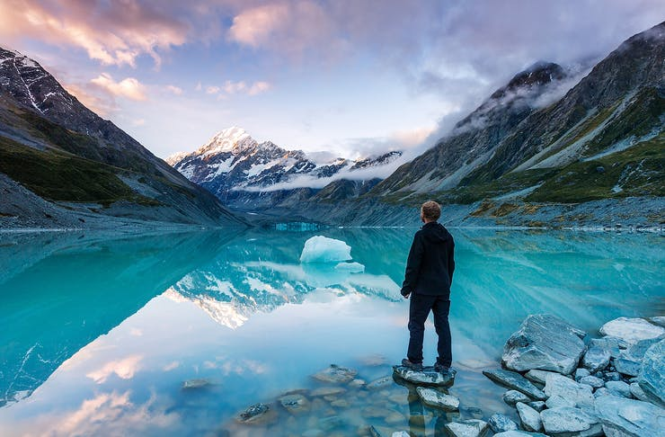A hiker looking at Mt Cook from lake with iceberg, New Zealand