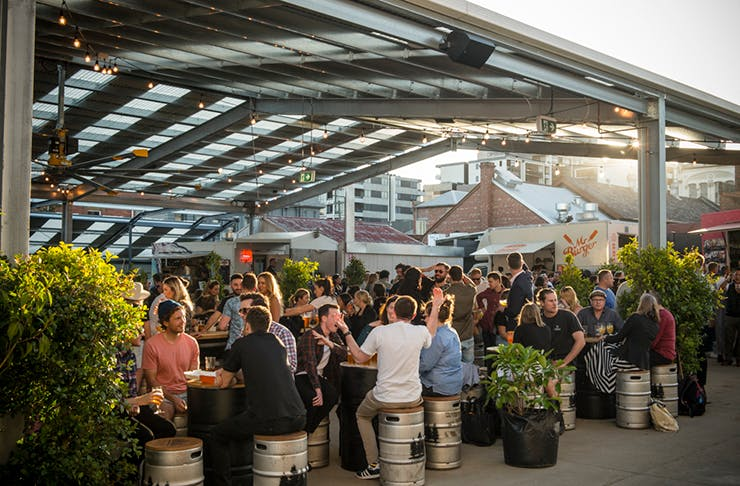 The outdoor beer area of Welcome To Brunswick with people seated at the tables drinking and talking