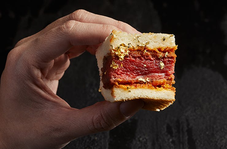 A hand holding up a sandwich filled with a rare cooked steak.