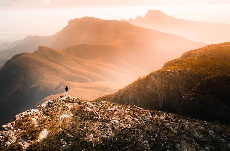 A man stands atop a mountain in the Stirling Ranges surrounded by mist.