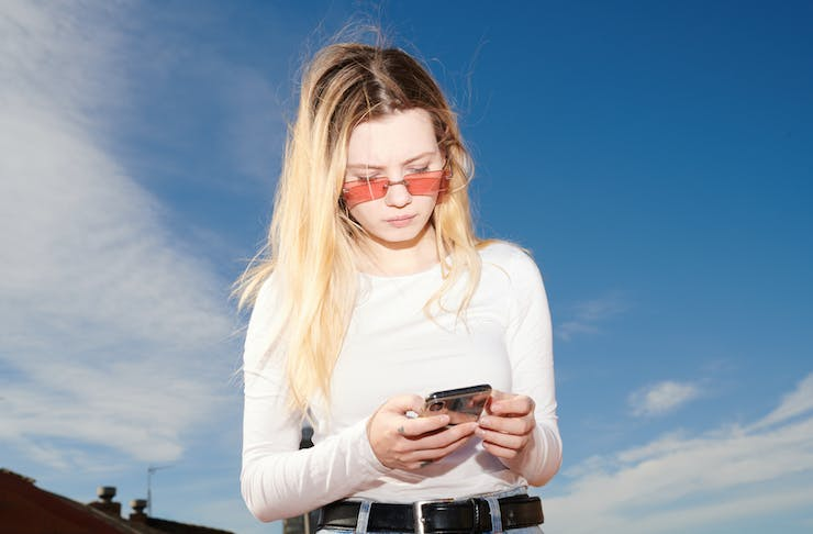 A blonde woman wearing a pink top and glasses glances down at her phone.