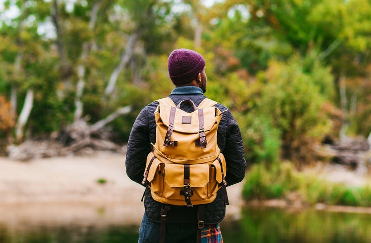 A man in a maroon beanie with a bright yellow backpack looks out onto a nature reserve.