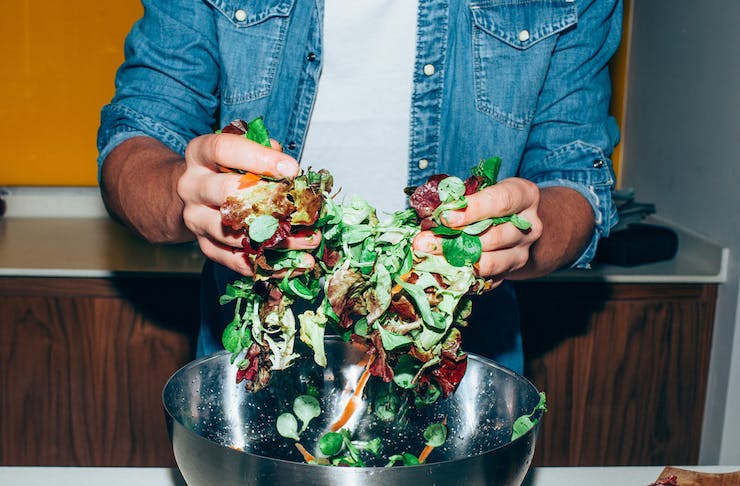 A man in a white t-shirt and blue denim shirt tossing a vibrant salad with his hands in a silver bowl.