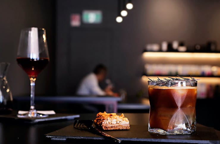 A coffee cocktail in a short glass sits in the foreground with a sweet slice. A glass of wine is in the background.