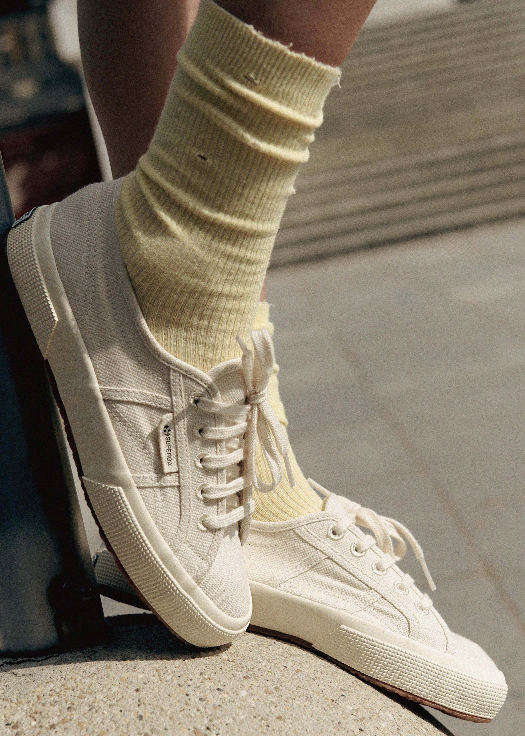 Milky white sneakers paired with yellow socks.