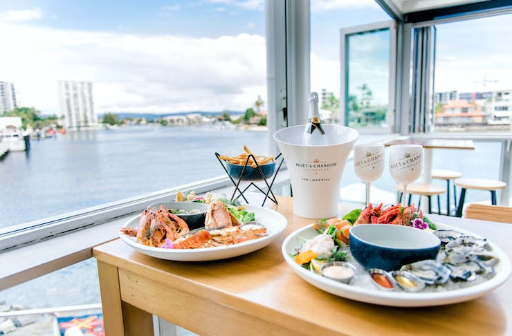 champagne and seafood on a table with waterfront views