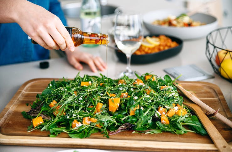 A green salad served on a wooden board.