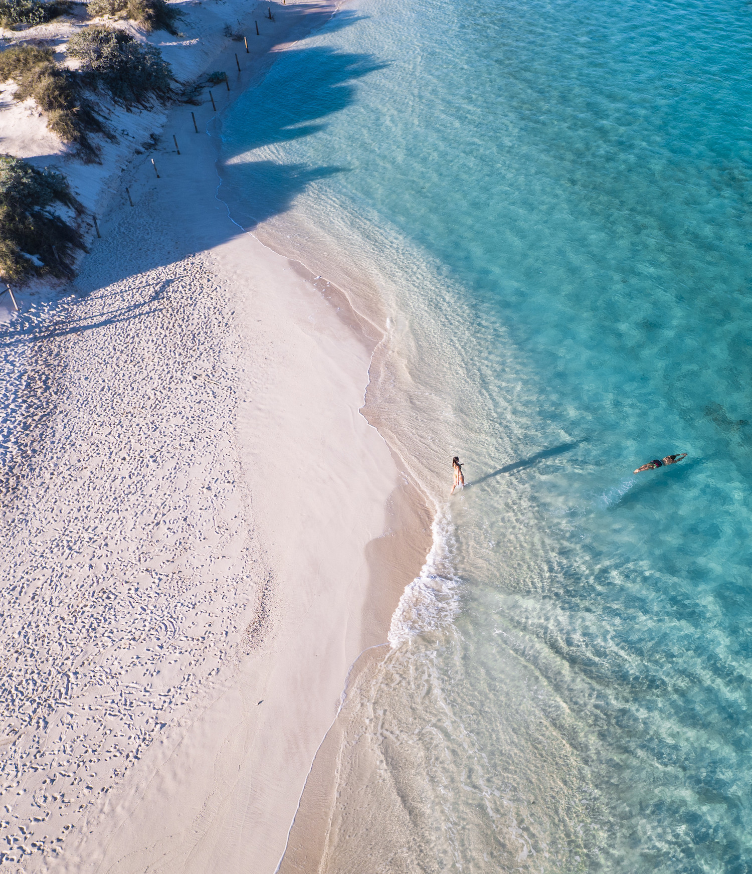 An aerial shot of two people swimming in crystal clear waters.
