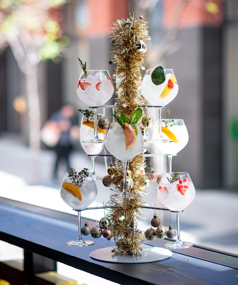 A drink tower filled with gin and tonicas and decorated with tinsel and baubles