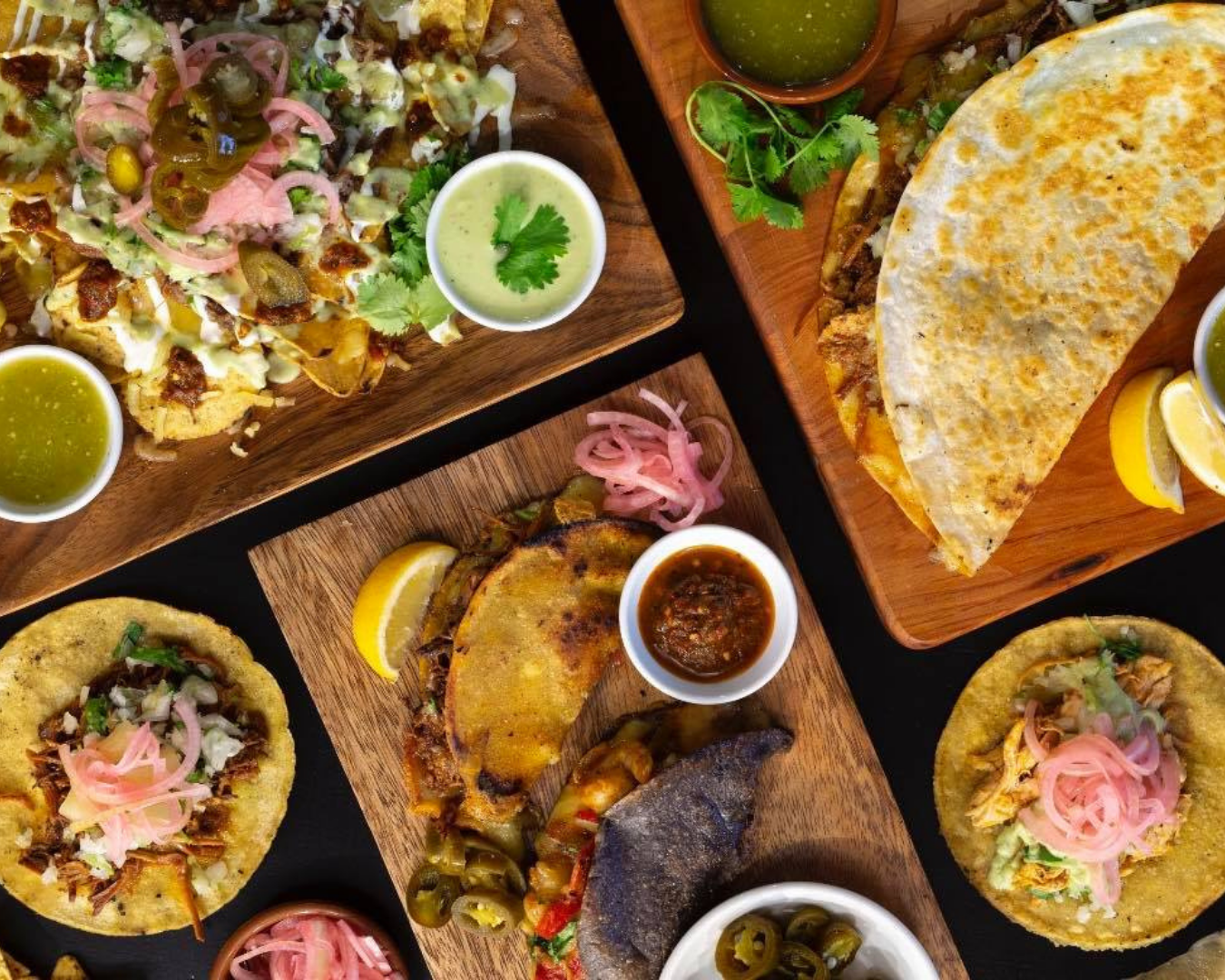 A range of dishes including Birria Tacos, Quesadillas and other tacos along with sauces and sides
