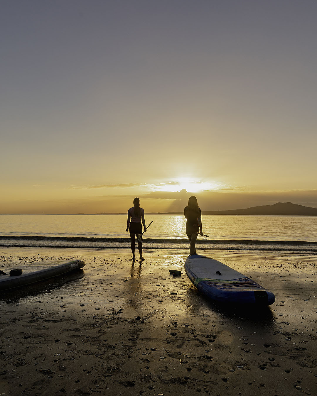 Women preparing for a morning paddle board on Takapuna Beach.