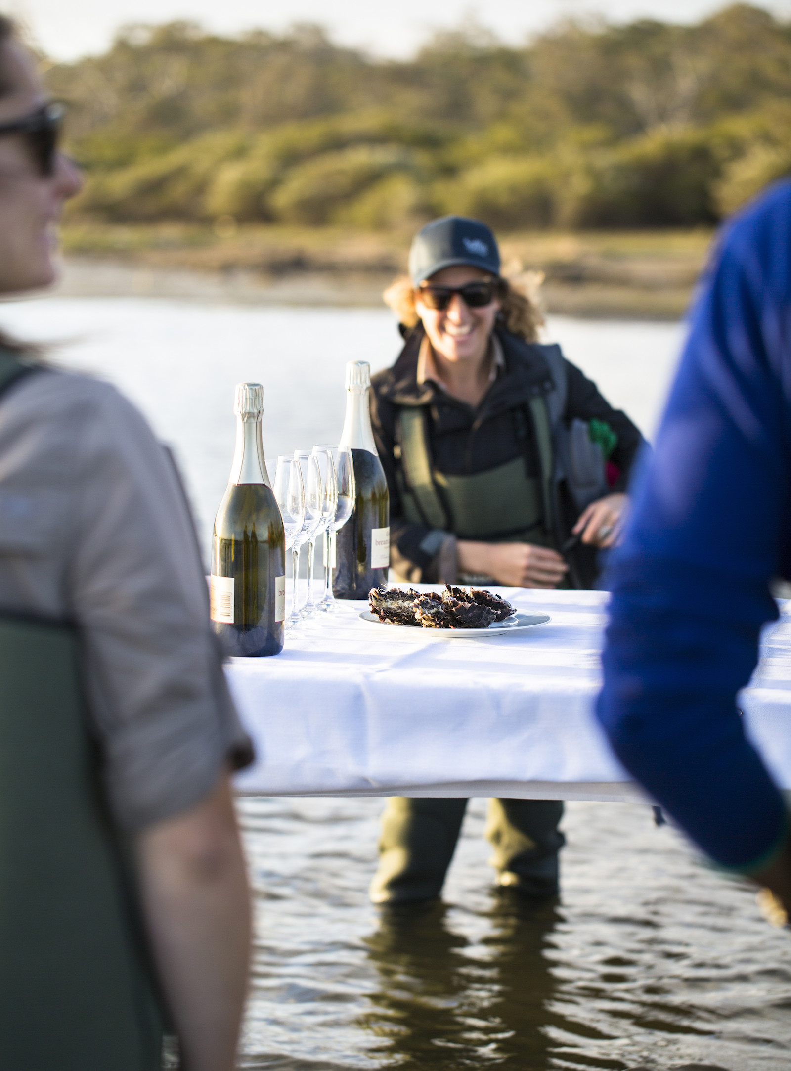 An oyster farmer wades in the water as they chat to guests.