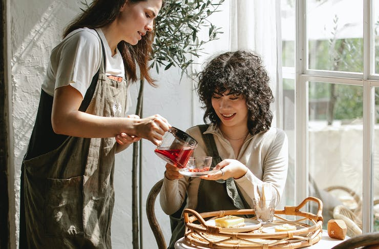 One girl pouring another crimson coloured tea.