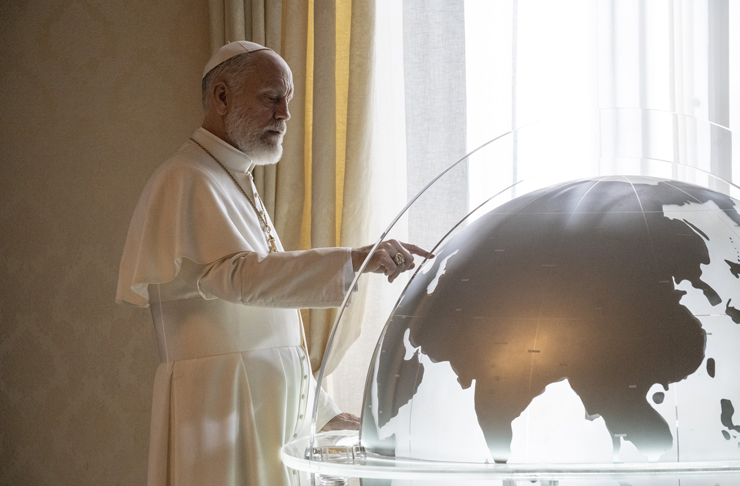 The New Pope dressed head to toe in white, holy garments gazes into a globe, over looking his flock