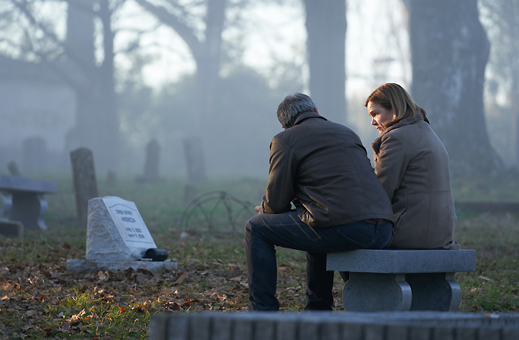 A couple with their backs to the camera stare at a headstone of a grave