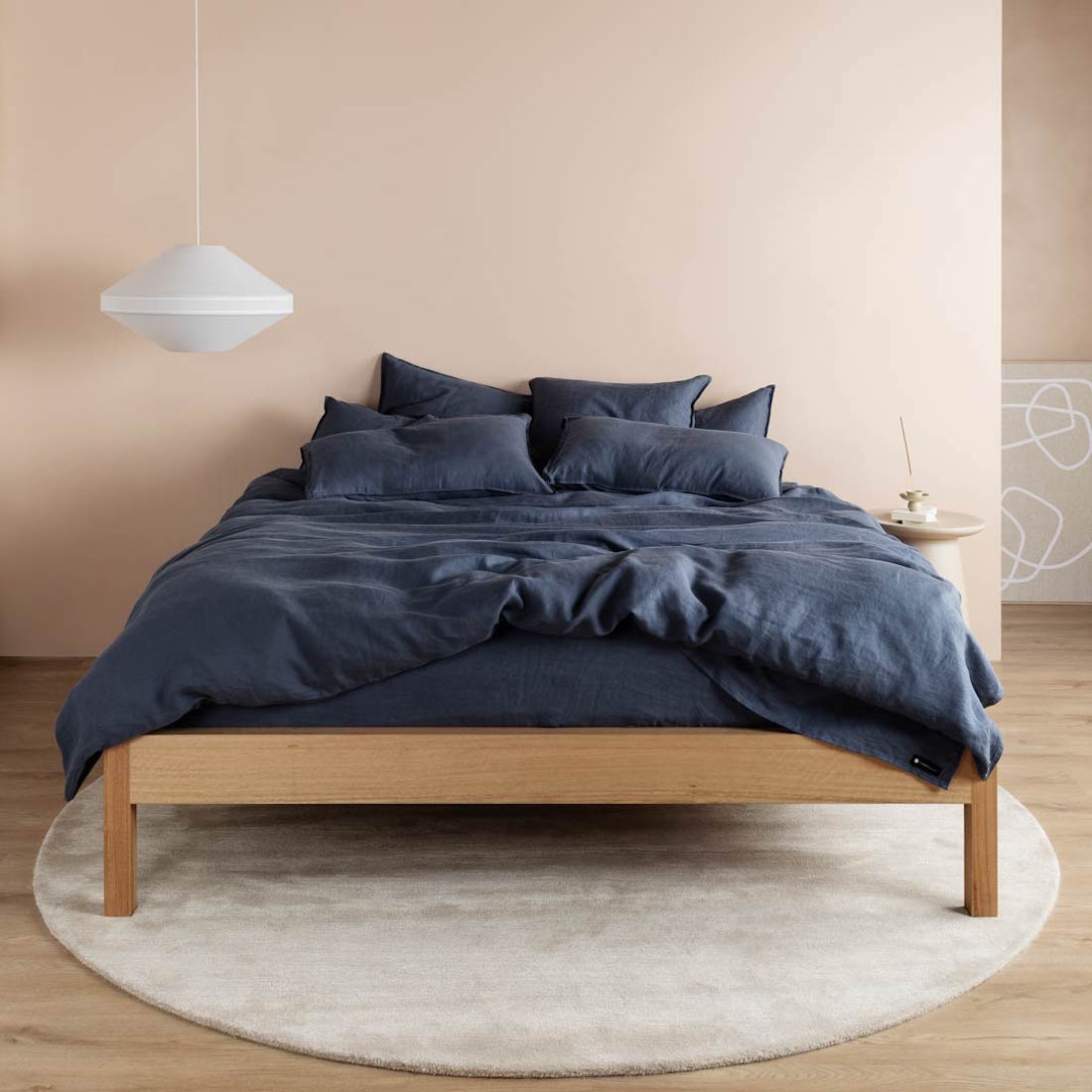 A bed with navy sheets looks cosy in a pink room.