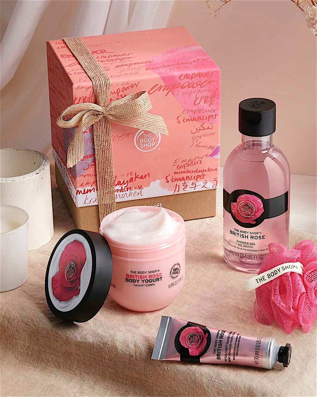 A pink and black bottle of shower gel and a pink tub of body yogurt are laid in front of a pretty pink box.