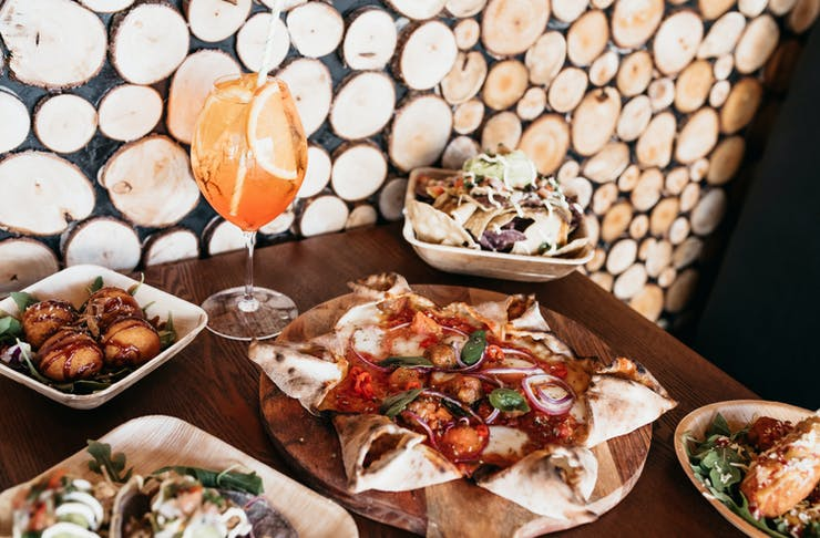 A table filled with cocktails, pizza, tacos and arancini balls behind a backdrop of a wooden wall.