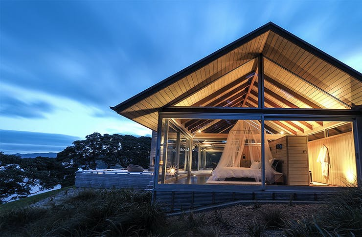 A view of the stunning glasshouse accommodation, showing a house overlooking the water.