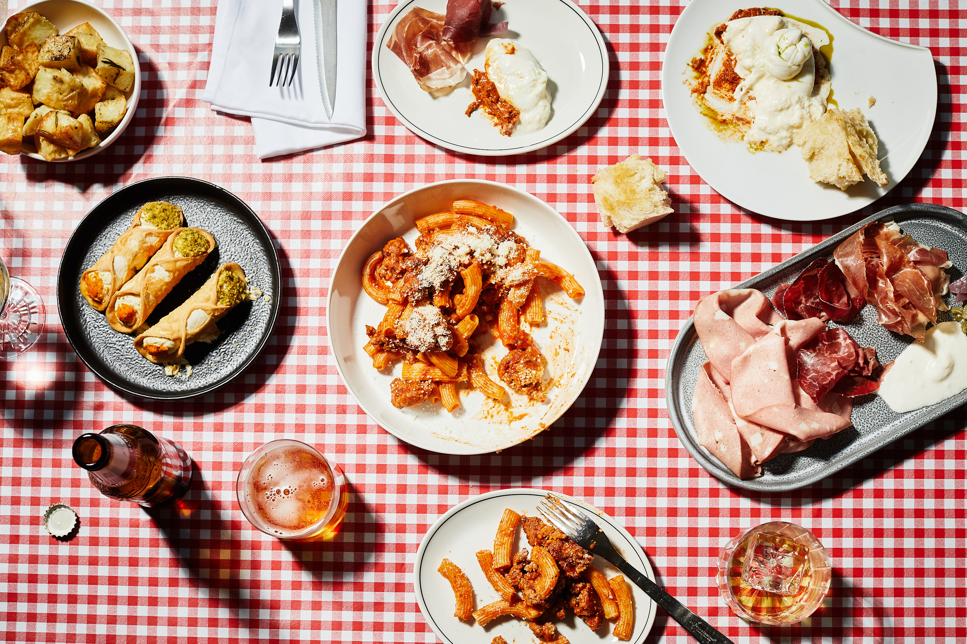 A top-down view of a classic Italian feast on top of a tartan table cloth.