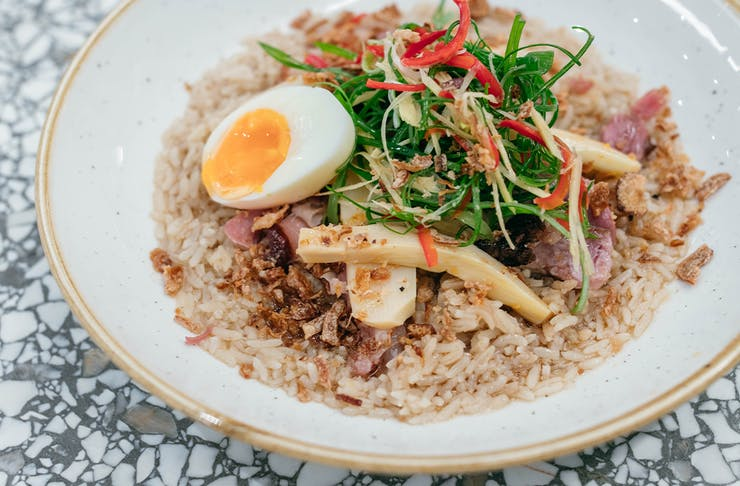 a bowl of rice congee topped with egg and bamboo