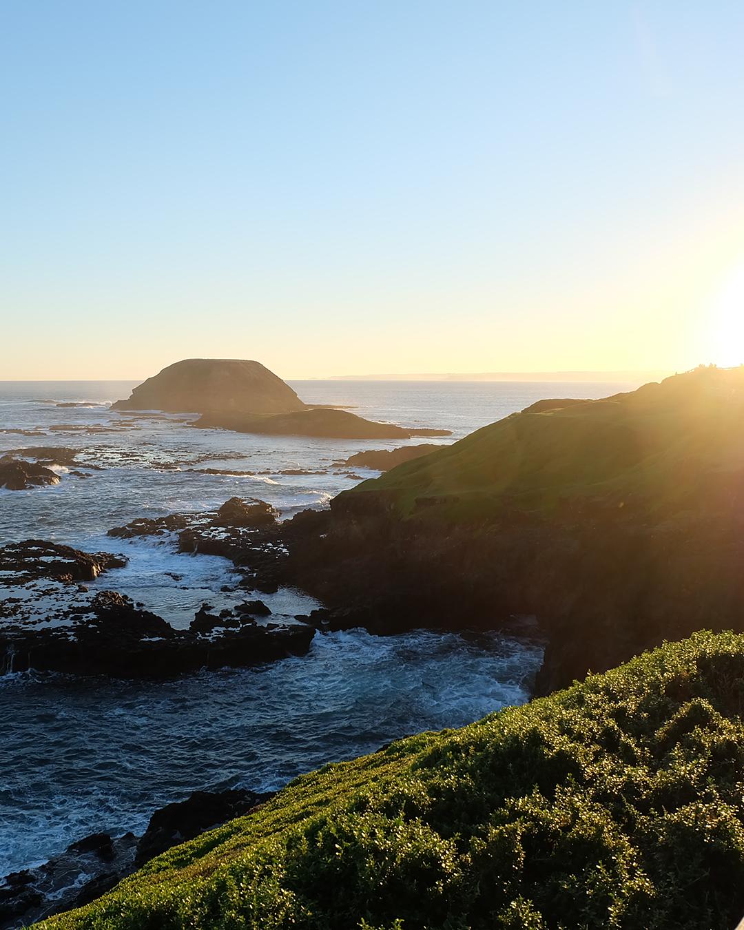 a stunning craggy coastline juts into blue ocean below.