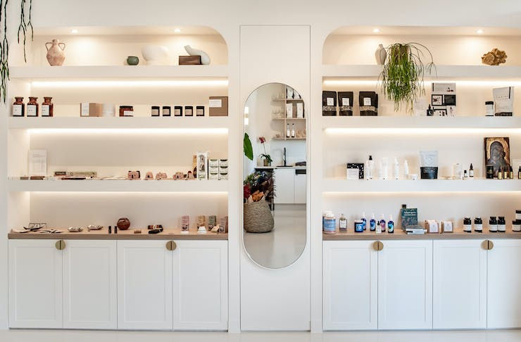 White custom-made shelves are filled with wellness and clean beauty products at The Orangerie in Noosa, QLD.